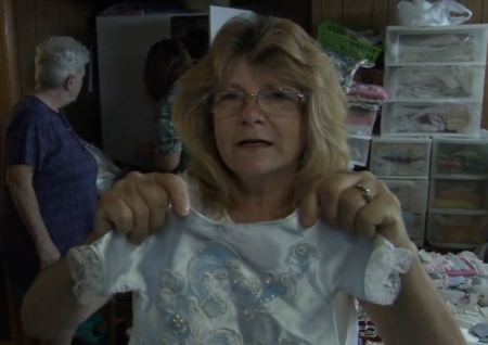 Dawn Lafferty holds an Angel Gown (image: screen grab from Detroit News report)